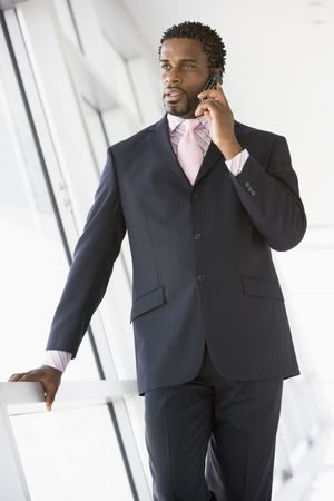 Businessman standing in corridor using cellular phone photo