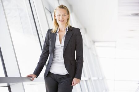 early thirties: Businesswoman standing in corridor smiling