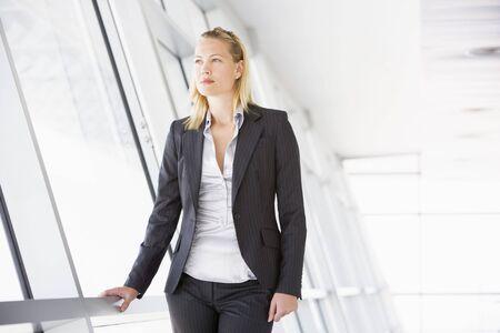Businesswoman standing in corridor photo
