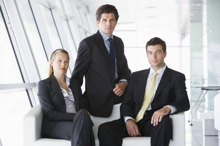 Three businesspeople sitting in office lobby photo