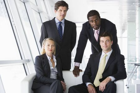 Four businesspeople in office lobby photo