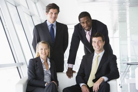 Four businesspeople in office lobby smiling photo