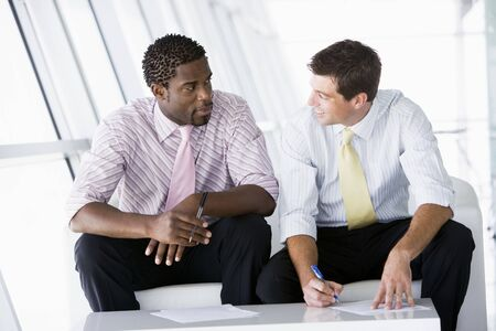 dos personas conversando: Dos hombres de negocios sentado en oficina de lobby de hablar y sonriente