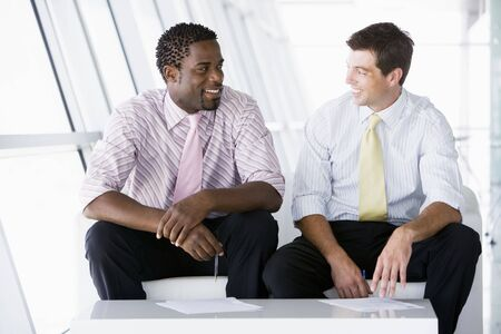 informal: Two businessmen sitting in office lobby talking and smiling