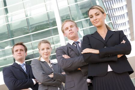 Four businesspeople standing outdoors smiling photo