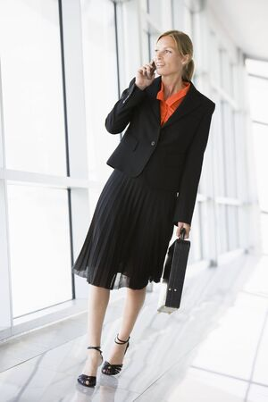 Businesswoman walking in corridor talking on cellular phone photo