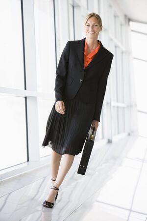 Businesswoman walking in corridor smiling photo