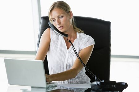 Businesswoman sitting in office with laptop on telephone Stock Photo - 3460093