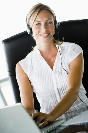 Businesswoman sitting in office wearing headset using laptop and smiling