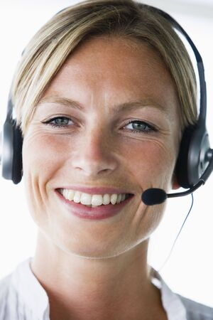 offset angle: Businesswoman in office wearing headset and smiling