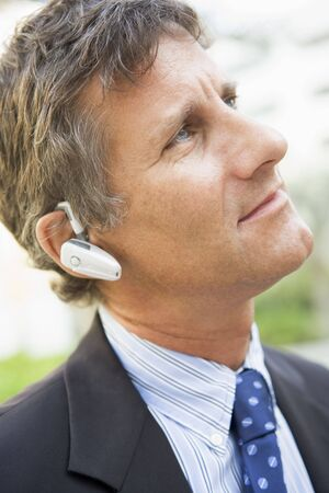 Businessman wearing headset outdoors photo