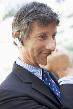 Businessman wearing headset outdoors photo
