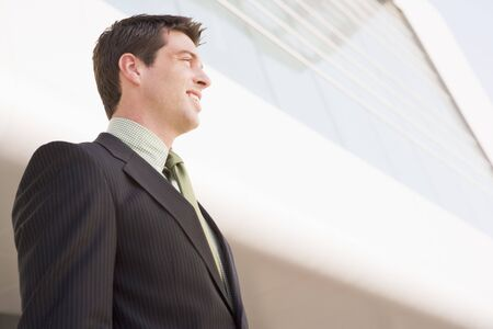 Businessman standing outdoors by building smiling Stock Photo - 3460012