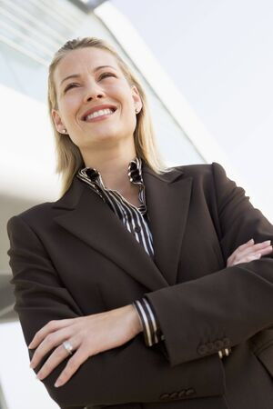 offset angle: Businesswoman standing outdoors by building smiling Stock Photo