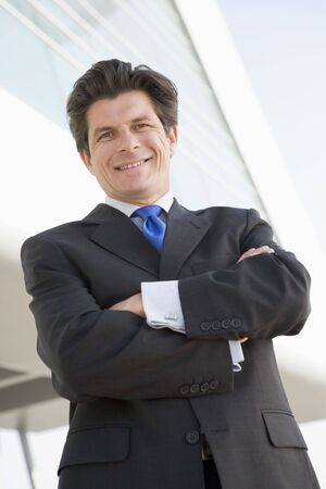 Businessman standing outdoors by building smiling Stock Photo - 3460016