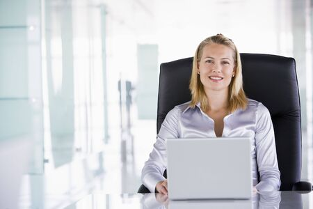 schedulers: Businesswoman sitting in office with laptop smiling Stock Photo