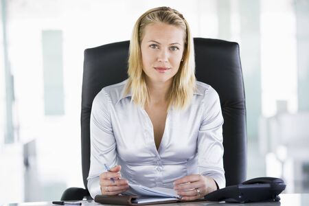 Businesswoman sitting in office with personal organizer photo