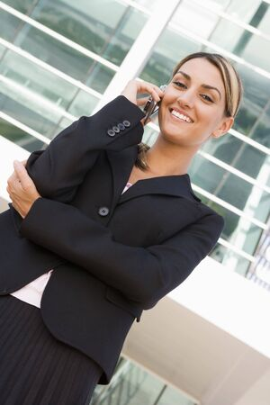 Businesswoman standing outdoors on cellular phone smiling photo