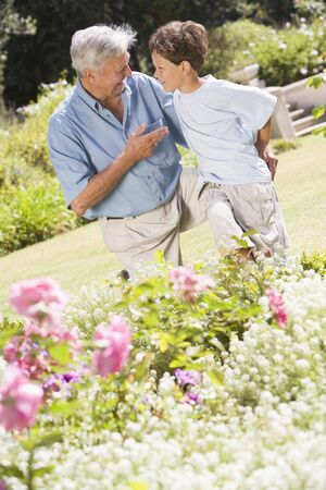 Grandfather and grandson outdoors in garden talking and smiling photo