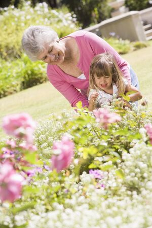 Grandmother and granddaughter outdoors in garden smiling photo