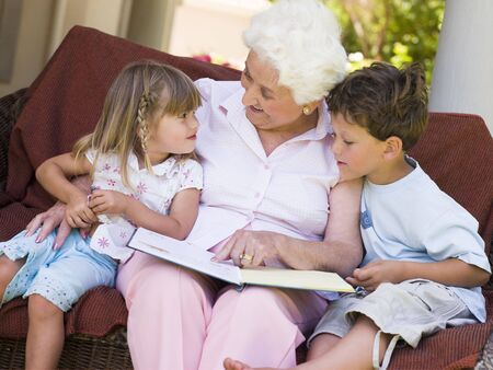 grandmother and grandson: Grandmother reading to grandchildren. Stock Photo
