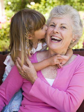 abuelos: Abuela obtener un beso de nieta.  Foto de archivo