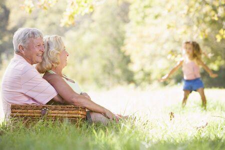 abuelos: Abuelos en un picnic con chica en el baile de fondo Foto de archivo