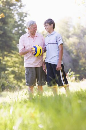 Grandfather and grandson at a park holding a ball and smiling photo