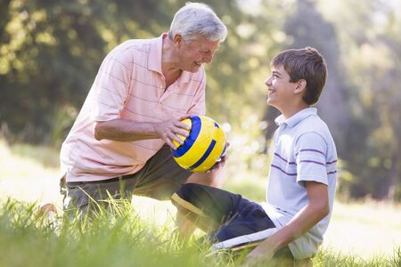Grandfather and grandson at a park with a ball smiling photo