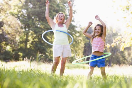 Grandmother and granddaughter at a park hula hooping and smiling photo