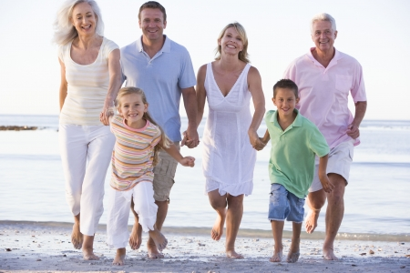 Extended family walking on beach photo