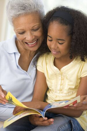 grandparent: Grandmother and granddaughter reading and smiling Stock Photo