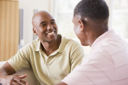 friends talking: Two men in living room talking and smiling