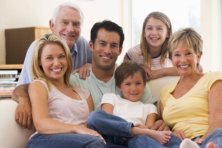 family on couch: Extended family in living room smiling