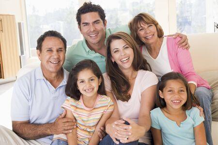 Familia extensa en sala sonriendo Foto de archivo