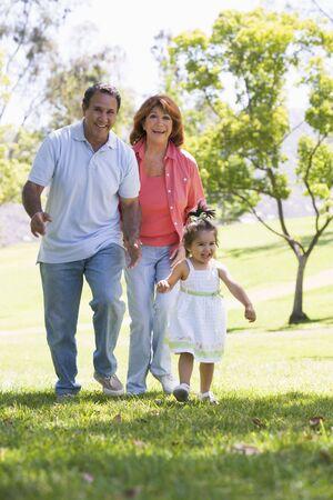 senioren wandelen: Grootouders lopen in park met kleindochter