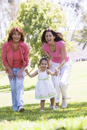 Grandmother with adult daughter and granddaughter in park photo