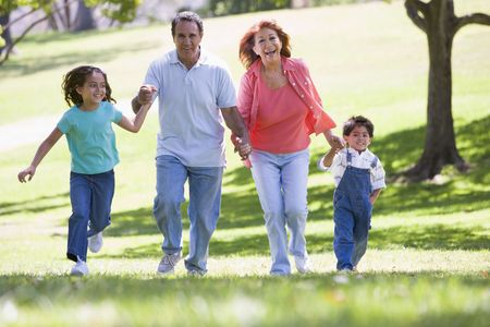 grandkids: Grandparents running with grandchildren. Stock Photo