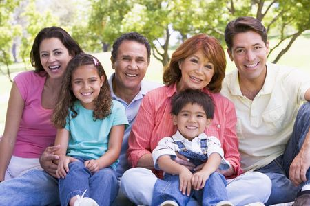 extended: Extended family sitting outdoors smiling Stock Photo