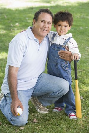 Grandfather and grandson holding baseball bat and smiling photo