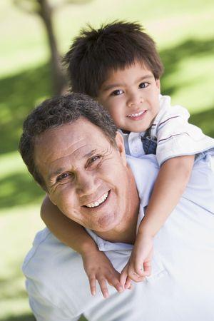 grandfather and grandson: Grandfather piggryback riding grandson.