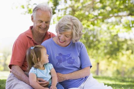 grandparent: Grandparents with granddaughter in park Stock Photo