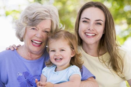 Grandmother with adult daughter and grandchild in park photo