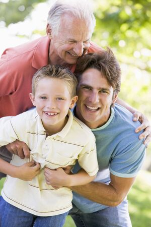 sons and grandsons: Grandfather with adult son and grandchild in park