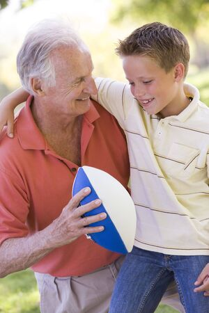 Grandfather and grandson outdoors with football smiling Stock Photo - 3460366