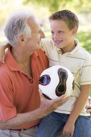 close together: Grandfather and grandson outdoors with ball smiling