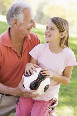 Grandfather and granddaughter outdoors with ball smiling photo