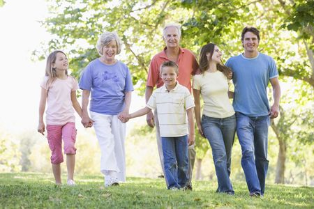 a generation: Extended family walking in park holding hands and smiling Stock Photo