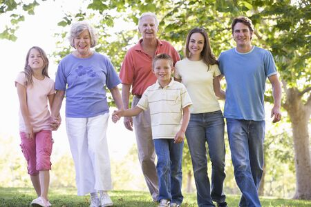 multi generation: Extended family walking in park holding hands and smiling Stock Photo