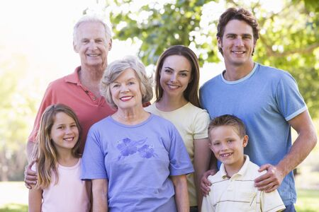 extended: Extended family standing in park smiling Stock Photo